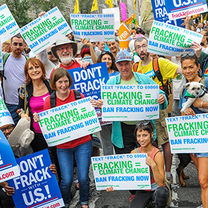 Activists holding signs calling for a national ban on fracking.
