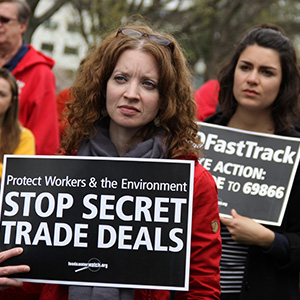 Activists march with signs protesting the Trans-Pacific Partnership trade agreement.
